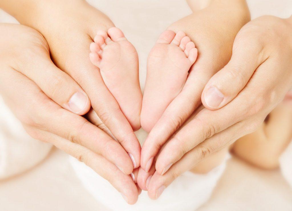 ידיים של אמא מחזיקות רגליים של תינוק