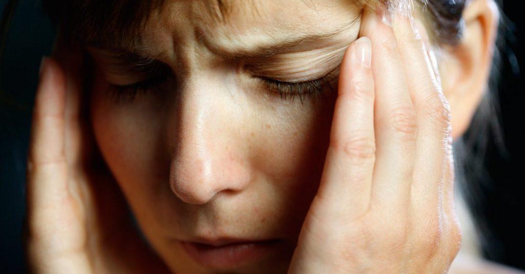 אשה תופסת את הראש סובלת ממגרנה